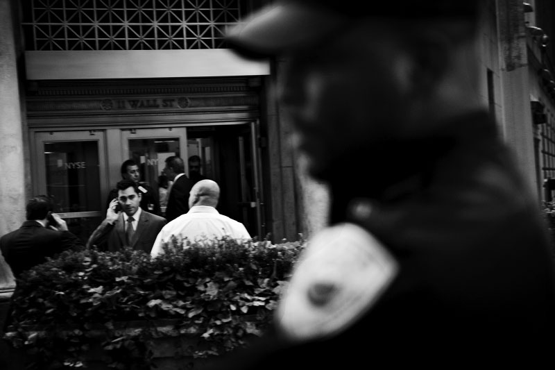 Traders call outside of the New York Stock Exchange as the share prices plunge, while a security guard is nearby on Oct 02 2008. Three days before on the week, The Dow fell a record 778 point, and the financial crisis seems to go deeper despite the fact that on the later night, the US Senate passed the 700 billion dollar package to bail out the beleaguered US financial sector -- so did the House next day (Oct 03).