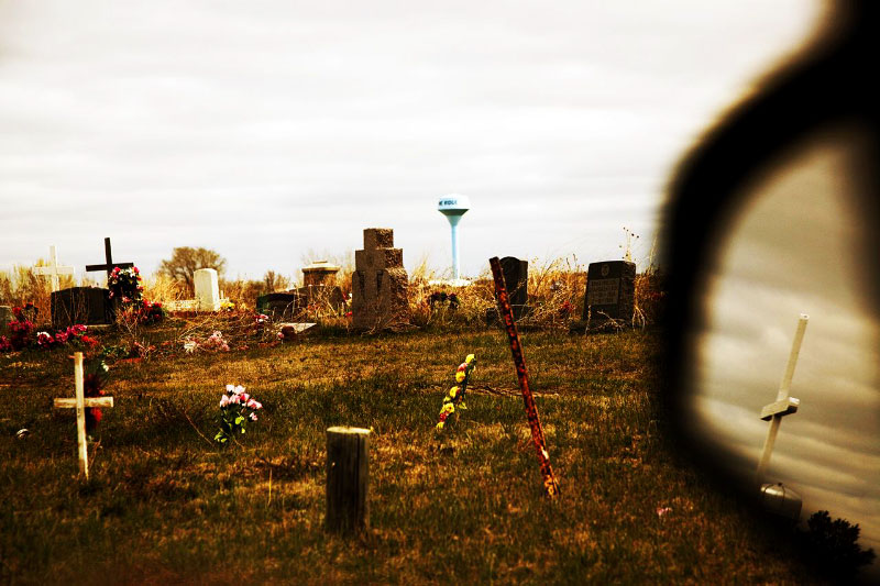 A scene of cemetery; Due to the fact that the practice of native American religious ceremonies had been banned in the late 19 century to the 1970s, many Lakota people are Christians, though now the youths have started to have their own traditional faith.