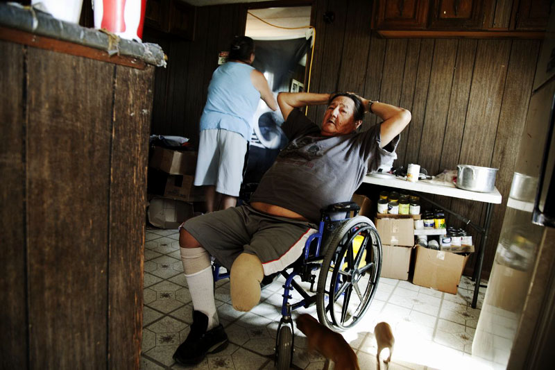 Dewey Brave Heart, 61year old veteran, who got amputated due to diabetes, and his wife June, 52, stay at the kitchen of their trailer-house where13 people altogether live and it is very damageable if strong wind hits it.