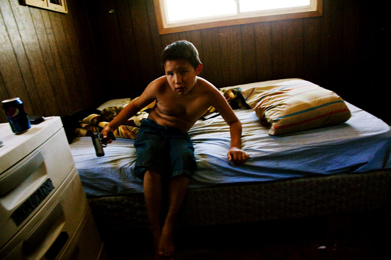 10 year old Lakota boy Joey stays at a bed with BB-gun. He has been adopted from an alcoholic mother by his aunt.