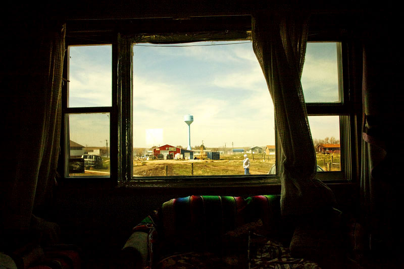 A desolate scene of a town of Wanblee in the Pine Ridge reservation, through a window of a Lakota family.