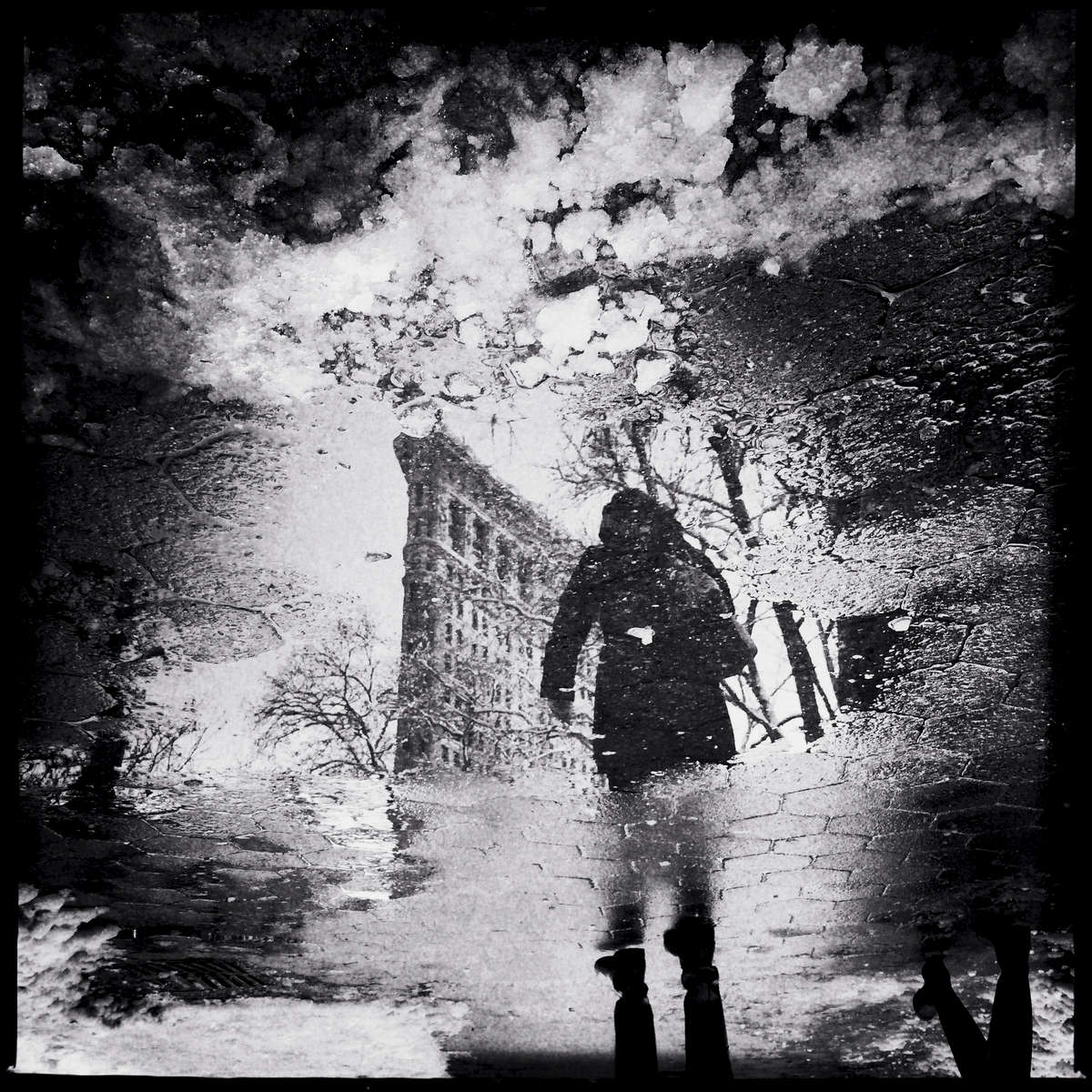 Snowy puddle reflection with a man and Flatiron building.