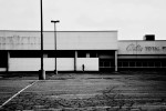 A man walks in front of a closed down store in a Detroit shopping mall, though some of the stores are still open, the parking lot is deserted. March 2008.