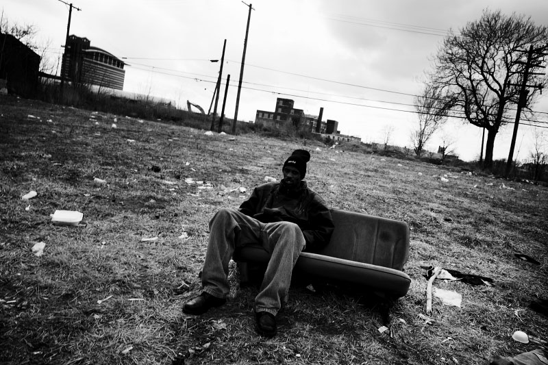 A homeless man sits on a sofa, that was a part of a car, in an abandoned, burned out empty lot in Detroit Downtown. March 2009.