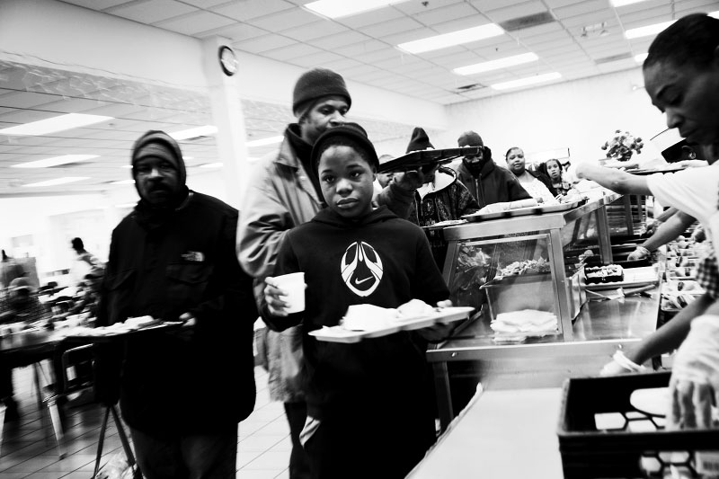 The homeless and the poor, including children,  make a line at the Capuchin soup kitchen.