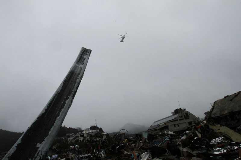 The destroyed scene of Onagawa due to the unprecedented tsunami in Japan, created by the March 11th magnitude 9 earthquake, while a Japanese  Navy copter is flying.