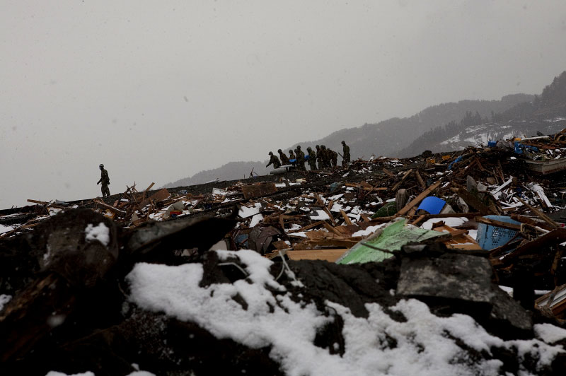 Soldiers of Japanese Army are carrying out a body, victim of the unprecedented quake and tsunami from the tsunami devastated site, Otsuchi, Iwate