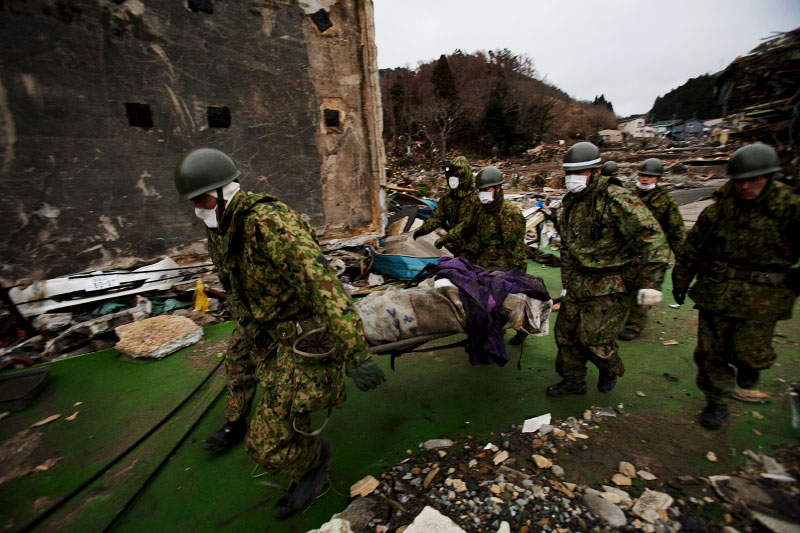 Soldiers of Japanese Army are carrying out a body, victim of the unprecedented quake and tsunami from, the site. Onagawa, Miyagi.