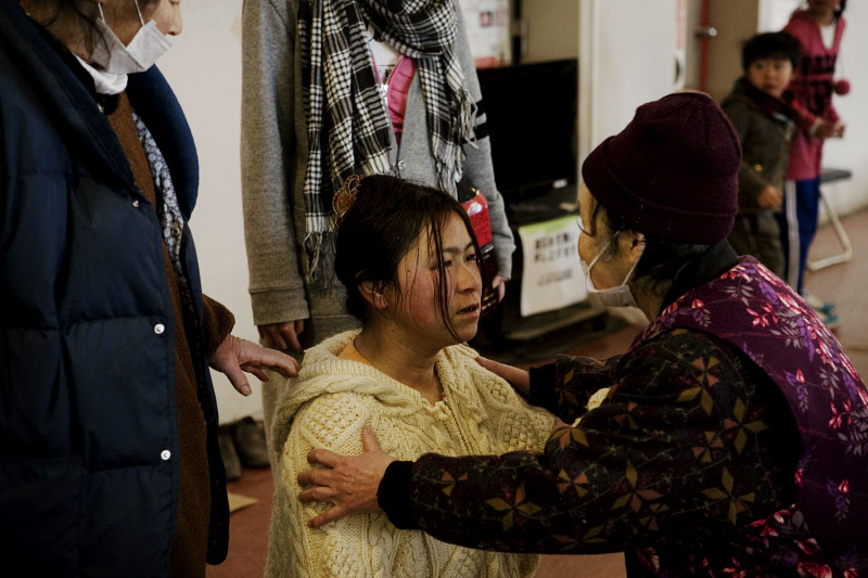 One of the tsunami survivors consoles another survivor, as many of them lost theri famifly members and homes, at an evacuation center in Onagawa, Iwate.