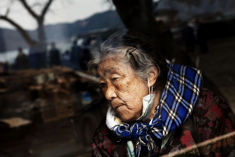 Tsunami survivor Sue Kurosawa, 84, stays at an evacuation center of Akaham school in Otsuchi, while other tsunami survivors are reflected on the glass.