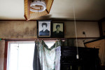 A tsunami damaged house, yet the photos of the passed away family of a victim still remain.