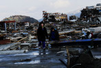 Two crying girls, survivors of the unprecedented tsunami, wander in the destroyed village of Minami-Sanriku. More than half of Minami-Sanriku's population have disappeared due to the tsunami.