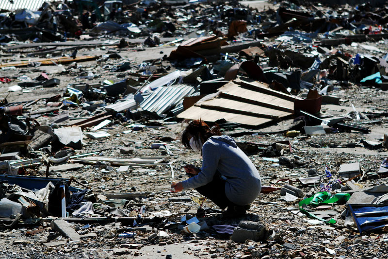 A female tsunami survivor is holding part of a china cup, as she is searching for any memorial items and anything worth at the debris of the tsunami destroyed house in Onagawa.