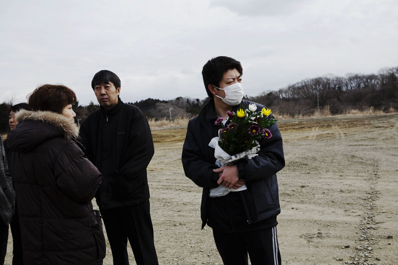 Family members of victims of the monster tsunami wait for the burial at a mass burial site in Oshio district in Higashi-Matsushima, Miyagi.