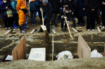 Family members of victims of the monster tsunami put sands onto coffins during the mass burial ceremony in Oshio district in Higashi-Matsushima, Miyagi.