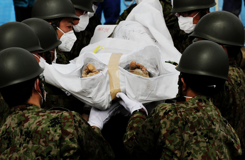 Japanese soldiers carry a victim of the monster tsunami into a mass burial site in Oshio district in Higashi-Matsushima, Miyagi.