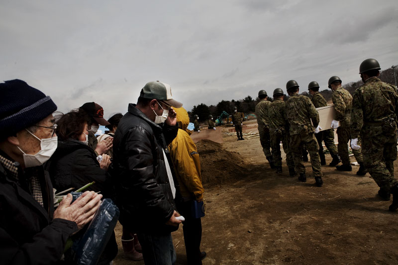 Family members of victims of the monster tsunami mourn during the mass burial ceremony, as Japanese Army carry a coffin, Oshio district in Higashi-Matsushima, Miyagi.