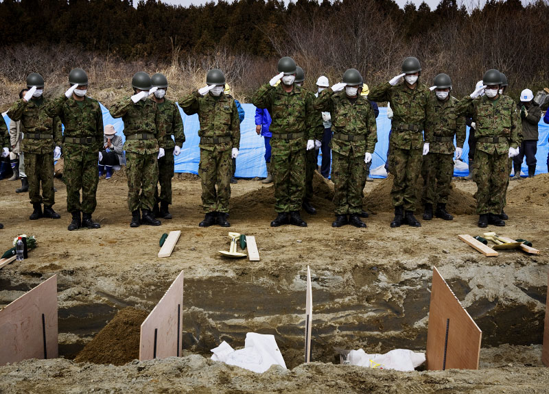 Japanese soldiers salute victims of the monster tsunami at a mass burial site in Oshio district in Higashi-Matsushima, Miyagi.