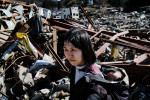 Tsunami survivor Hiroko Asanuma, 26, with her baby Ryo, is searching for any memorial items and anything worth at the debris of her tsunami destroyed house in Onagawa.