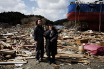 The cople -- Mitsuru Konno, 41, and his wife Sakiko, 47, stand in front of their tsunami destroyed house in Kesennuma.
