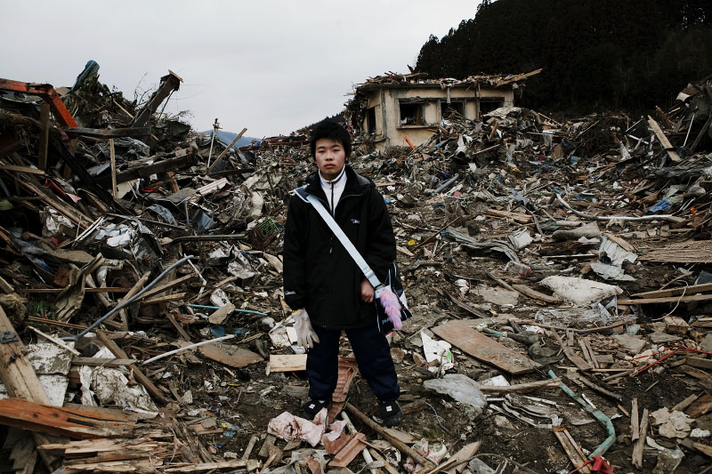 16 year old tsunami survivor Tsubasa Sudo stands at the debris near his destroyed house, as he comes back for the first time after the tsunami -- 3/11.