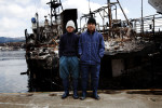 Tsunami survivors, Indonesian foreign students for the Japanese fishing industry, stand in front of a destroyed ship, Kesennuma, Miyagi.