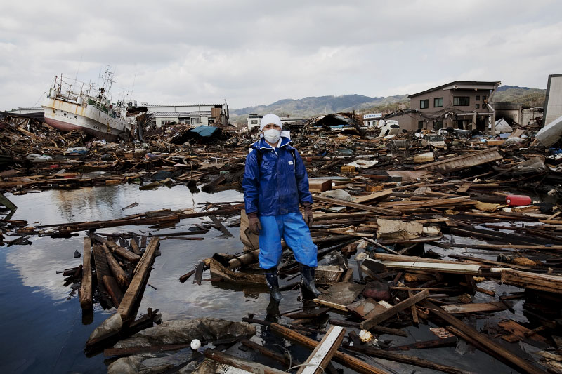 Tsunami survivor Yuji Takagi stands at the debris of his father's destroyed house, as he is searching for him, though probably the body. Kesennuma.