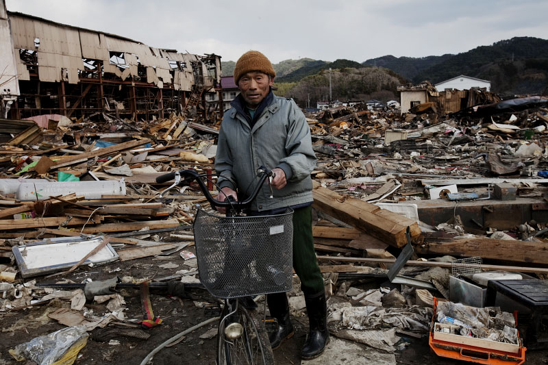 Tsunami survivor Takezo Iegashi 70, poses at the debris of his destroyed house, as he is searching for any memorial items and anything worth.