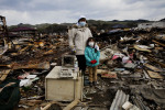 Tsunami survivor Akiko Takada, 33, and her daughter Mai, 5, pose at their destroyed house in Kisennuma, as they are searching for any memorial items and anything worth.