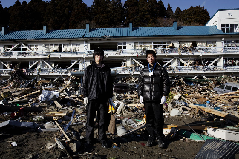 Tsunami survivors of high school students, Yuji Watanabe, 16, on the left, and Tatsuya Sasaki, 16, stand in front of the tsunami destroyed high school in Rikuzen-Takada.