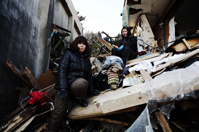 Tsunami survivors, Noriko Murakami, 44,  who lost  her husband, and her 12 year old daughter Ayumi pose at their tsunami destroyed house, as they are looking for any memorial items and anything worth.