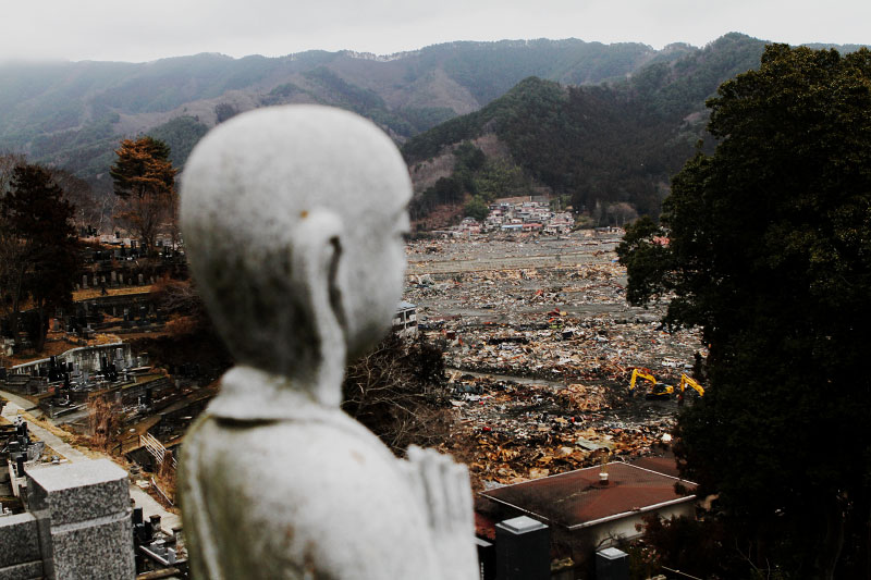A survived statue of a Buddha remains at a cemetery, as the tsunami destroyed areas of Otsuchi are seen downward.