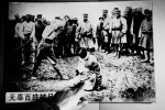 A volunteer Chinese guide points out her finger onto a photograph, saying that A Japanese soldier is executing an innocent farmer during the Japanese occupation of Manchuria. It hangs at a wall of the rebuilt Shuishiying where Japan and Russian signed a ceasefire agreement.