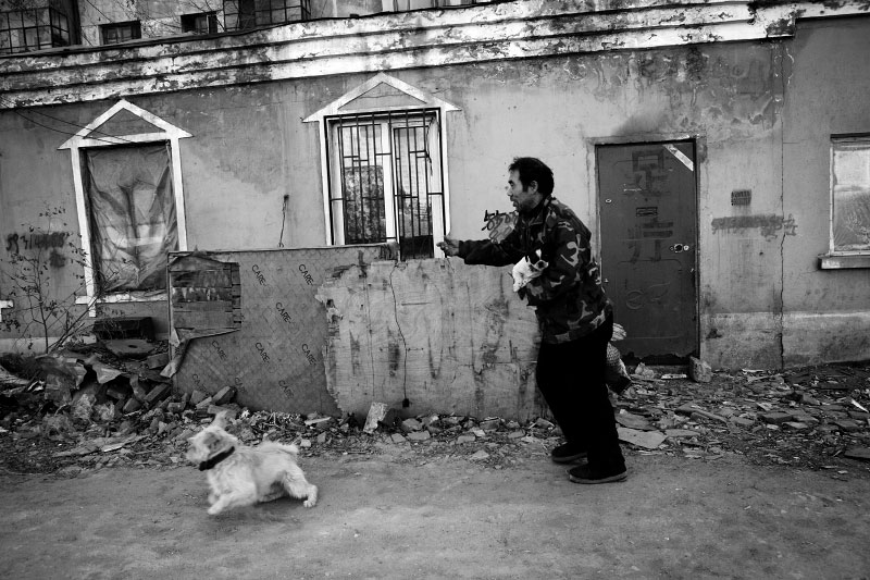 A man, calling himself Suon -- it means sun in English, plays with dogs in front of his house in the working class area that would be soon demolished to convert to luxurious residential buildings, in Harbin in China's North East. Like other areas in China, this region is in the real estate boom, but working class people are often grabbed their land unfairly.