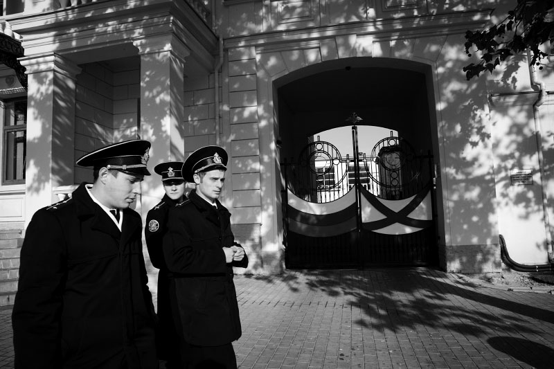 In Sevastopol in Crimea, Russian naval officers of the Black Sea Fleet pass in front of a Russians institute that shows symbolic colors and design of both Russia and the Black Sea fleet. Crimea is an autonomous republic of Ukraine, located in the south of the country on the Black Sea, and the majority is absolutely Russians. Russia has kept remaining the Black Sea Fleet in Sevastopol for over 200 years, even after Ukraine's 1991 independence. Although the fleet remaining is due to the two country's agreement, because of the status, Crimea has become one of the Russia-related potential flashpoints.