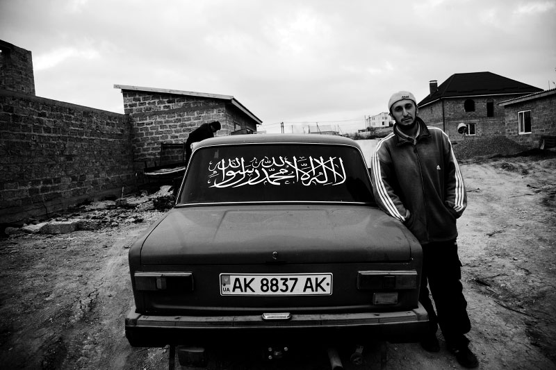 A Crimean Tatar stays next to his car that says {quote}God is great in Arabic,{quote} in Simferopol in Crimea. Tatars are minority in Crimea yet they used to virtually have their own country there, and many have come back from the forced exile, and now they demand their autonomy. Meanwhile, Crimea is an autonomous republic of Ukraine, located in the south of the country on the Black Sea, and the majority is absolutely Russians. Russia has kept remaining the Black Sea Fleet in Sevastopol for over 200 years, even after Ukraine's 1991 independence. Although the fleet remaining is due to the two country's agreement, because of the status, Crimea has become one of the Russia-related potential flashpoints. Nov 15 2008.