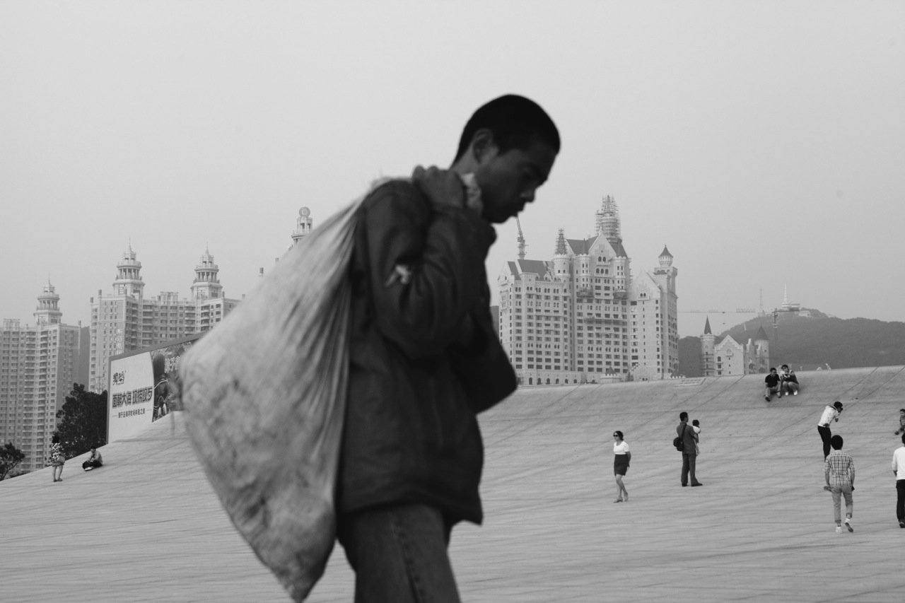 A homeless man walks at Xinghai Square adjacent to a newly built luxury residential area in Dalian, Liaoning province, in China's North East or Manchuria, as the region faces an uneasy economic boom, creating more materialistic culture and economic gap.China's North East was once called Manchuria. The region was at a crossroads that was manipulated in history, including the occupation by Russia and Japan. And now the area is facing upheavals due to the globalization with China's rapid economic growth itself, creating the gap between the rich and the poor and even more unemployment and worrying for the future.