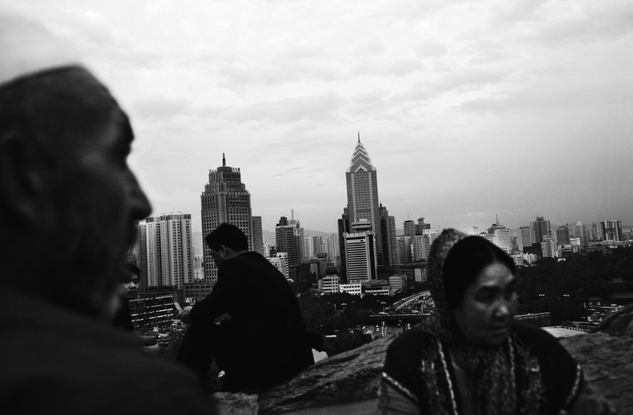 A Uighur couple and two Han Chinese men at an Urumqi park overlooking the province capital's new buildings where once oases and small merchant oriented markets existed.