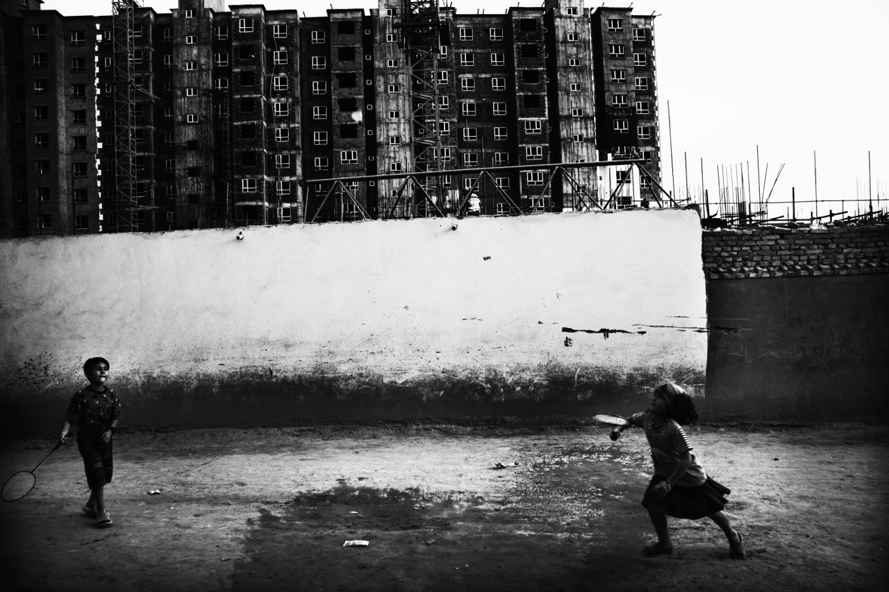 Uighur children play badminton near the construction site of high-storied modern buildings where a large scale of Uighur old communities once existed. Due to the Chinese modernization projects, much of the cultural, ethnic identity of Uighurs has been dying.