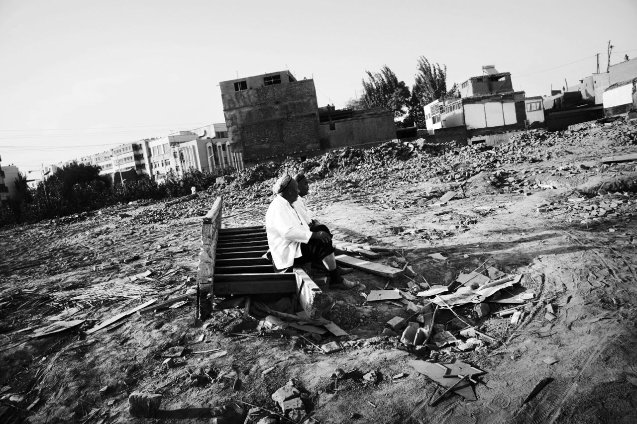 Two Uighur men are staying at their demolished and flattened community due to the Chinese modernization projects or Chinesefication, though the government insists the main reason is security of houses -- especially resistance to earthquake, in Kashgar, Xinjiang.