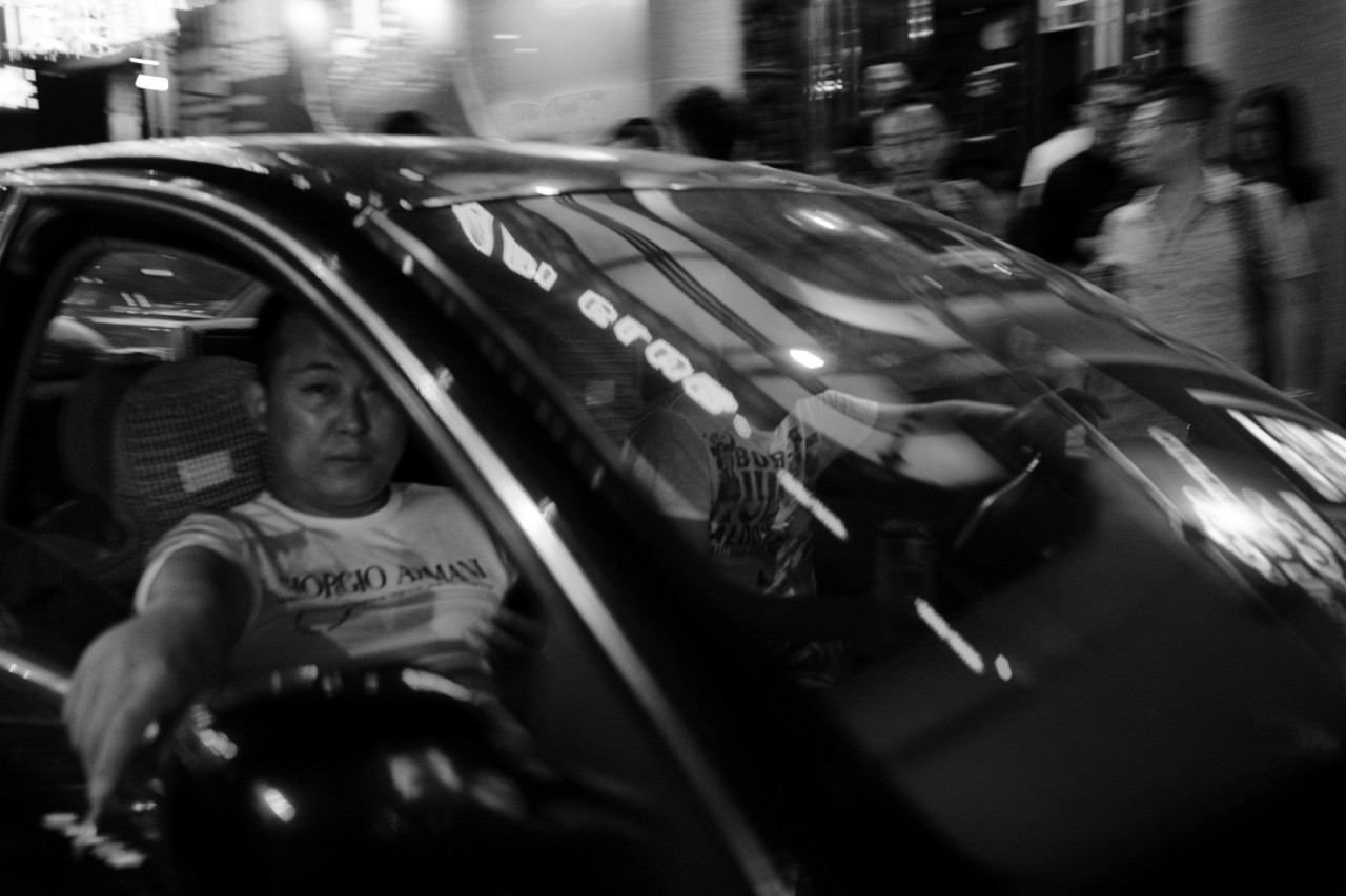 A Chinese man gives a sharp eyes from an expensive car of Audi, in famous/ infamous night spot Kundu in Kunming, the capital of Yunnan province, as China's massive economic development, as well as its migration, has created the outstanding gap between the rich and the poor in the recent years.