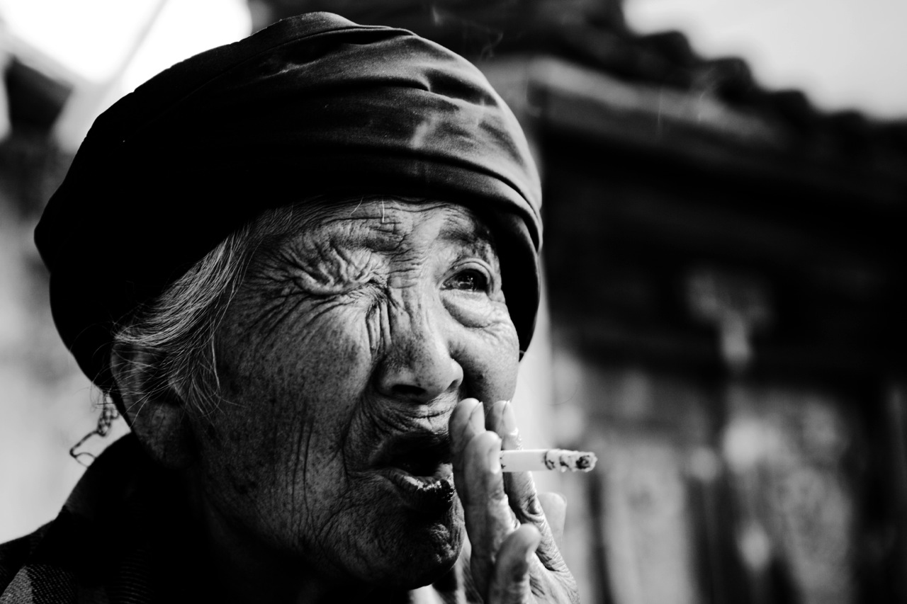A 80 year old ethnic Bai woman smokes in a village of Shaxi, as her eye and leg have medical problems, yet not treated well.
