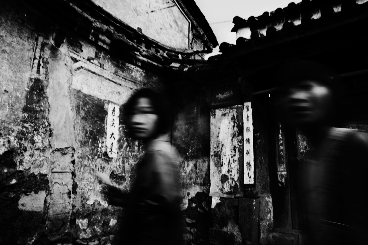 Ethnic Bai girls passes near an old house in Shaxi where many residents live in poverty. At the same time, their village would face demolition in the name of China's massive economic development project.
