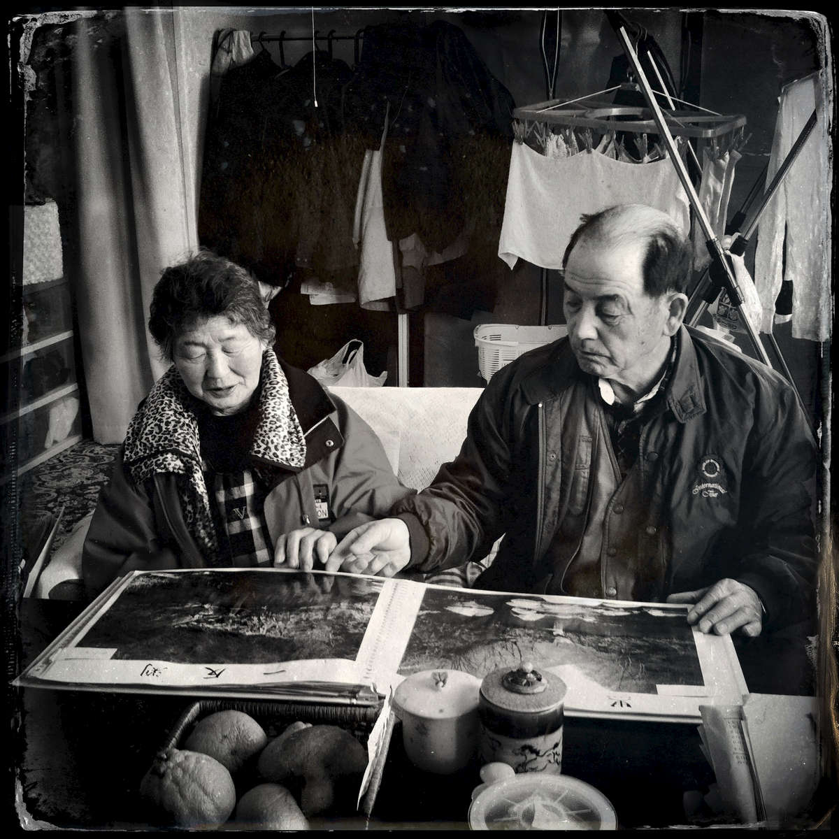 At their temporary housing, Fukushima's evacuees, Koshiro Konno, 76, and his wife Tamano, 75, look at photos of their home village's mountains and rivers that he photographed before the disaster. Now, virtually impossible to return due to hight radiation. Mar/11/2013, Motomiya.