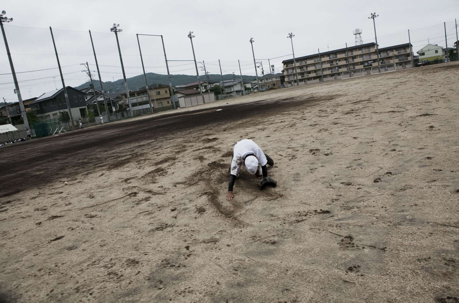 Kenta Yamaki, 17, whose grandmother died due to the tsunami and school was closed due to the Fukushima Daiichi nuclear disaster, falls down to the playground during the baseball training. Aug/ 2011, Fukushima-city.