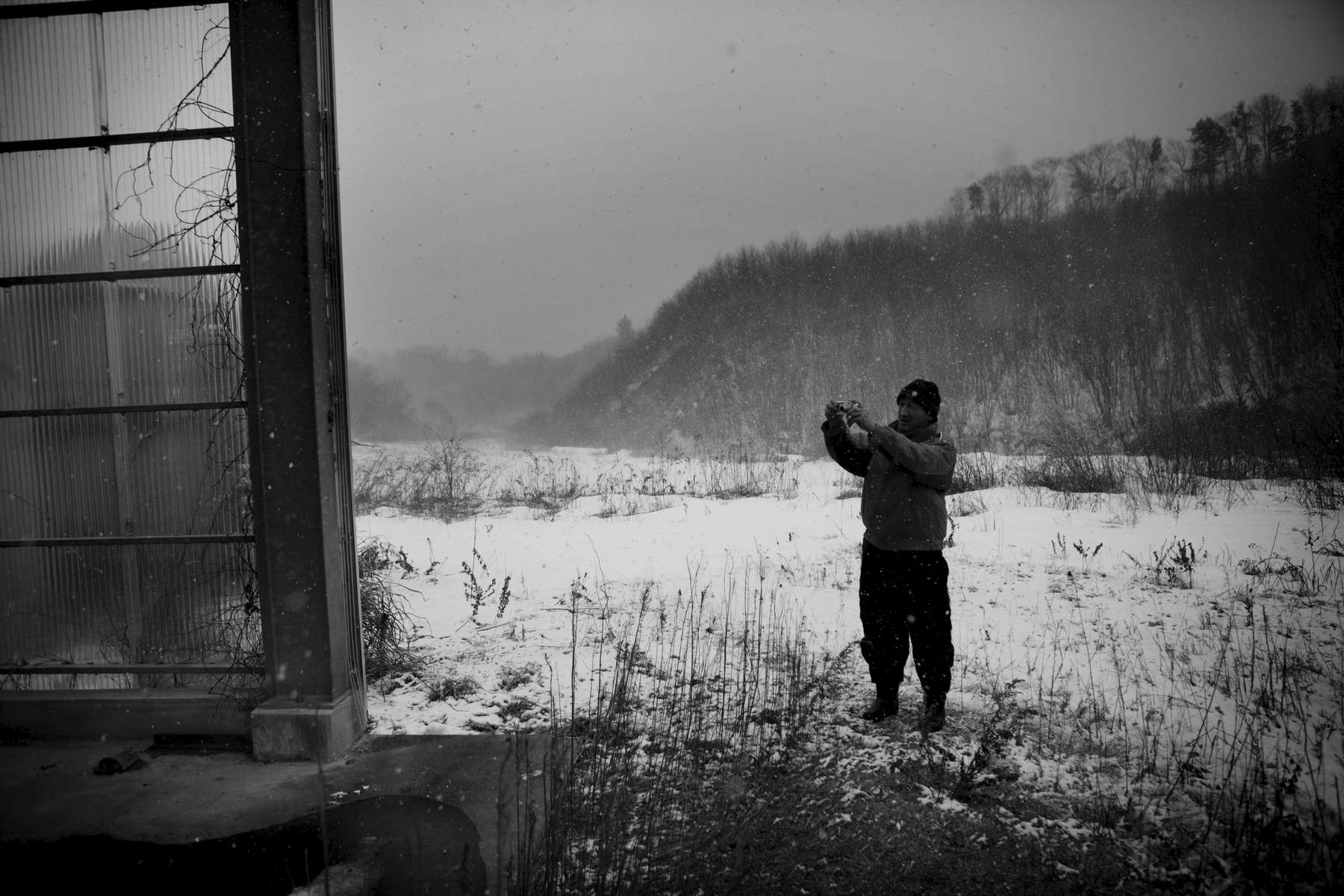 Dairy farmer ToshinorI Sanpei, 57, photographing a closed dairy farm cooperative compound in his radiation-contaminated village. Feb/ 2013, Tsushima, Namie.