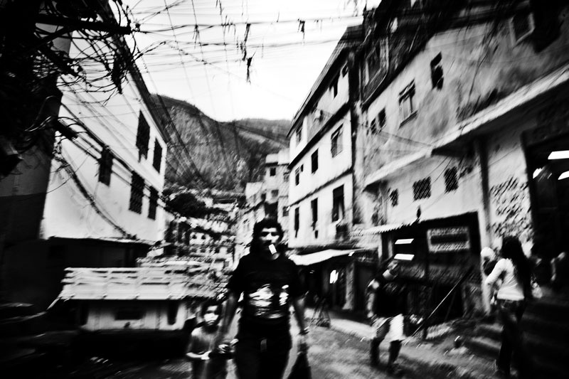 In Rocinha, the biggest favela or slum in South America, a father and his son pass trough a street where illegally picked up electric wires are dangerously exposed. May 2007.