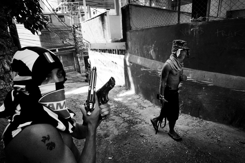 In Rocinha, members of ADA, or Amigos Dos Amigos, meaning Friends of Friends in English, stay in the alley during patrol to prevent the rival gangs and police from entering the community. May 2007.