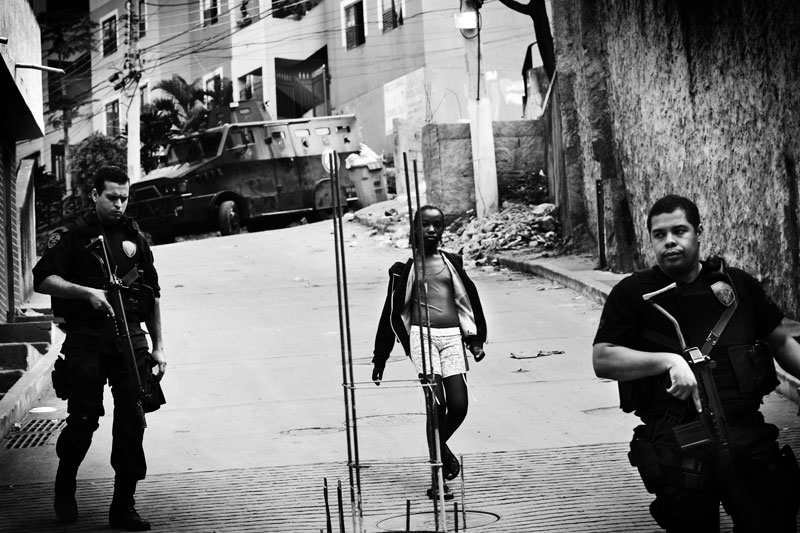 A young female resident in favela Mangueira passes near military police forces, who are in duty for the operation to capture mafia-like gang members of Comando Vermelho. May 2007.