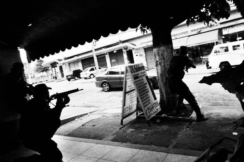 In Vila Cruzeiro, a favela, Military policemen are in the operation in order to capture mafia-like gang members of Comando Vermelho. Although it has been continuing more than three weeks, the capture is very tough, since the gangs are well-armed and the urban fighting could result in many innocent casualties. May 2007.
